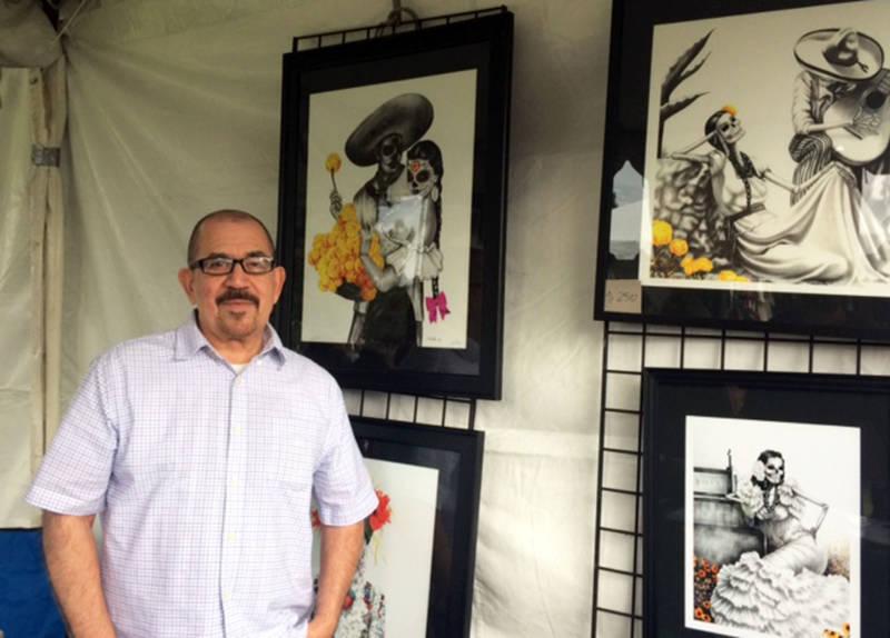 Los Angeles-based Chicano artist Hector Silva stands next to his ornate pencil sketches at Oakdale Memorial Park in Glendora for Dia de los Muertos Celebration.