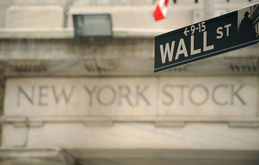 A Wall Street sign outside an entrance of the New York Stock Exchange.