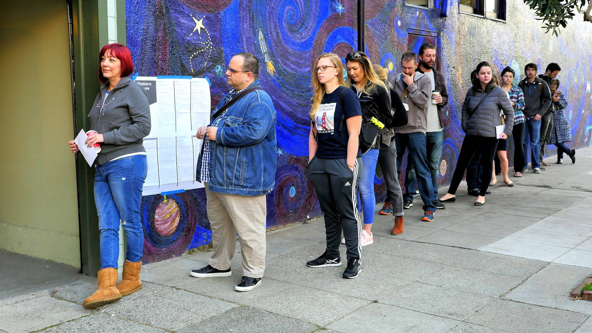 A line of voters wraps around a building in the Mission District. Sheraz Sadiq/KQED