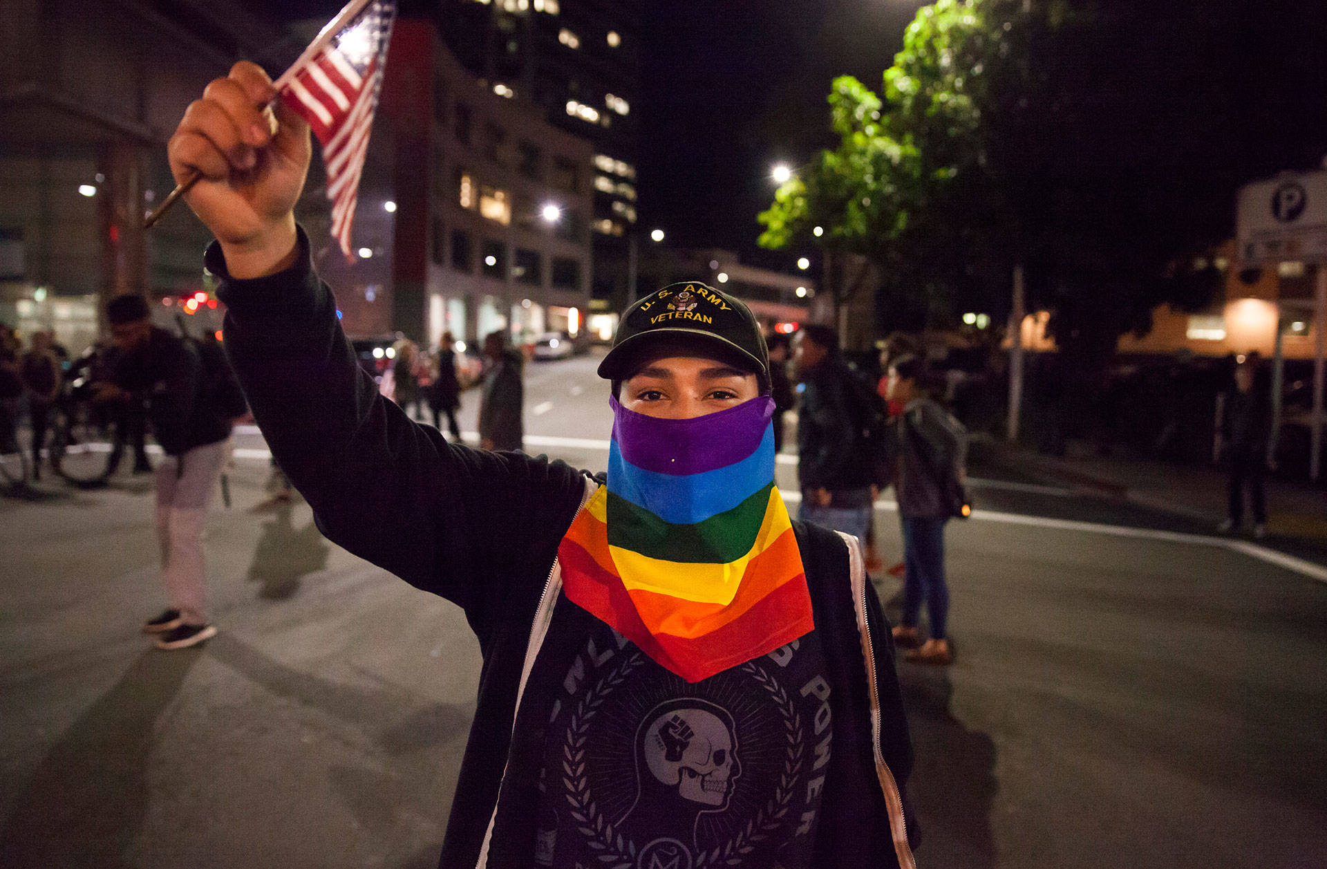 An anti-Donald Trump protester holds an American flag during a protest in Oakland last week.  Brittany Hosea-Small/KQED