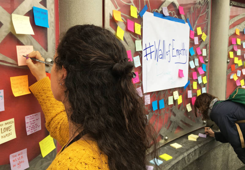 People attach messages of support and empathy to the walls at the 16th St. BART station in San Francisco.