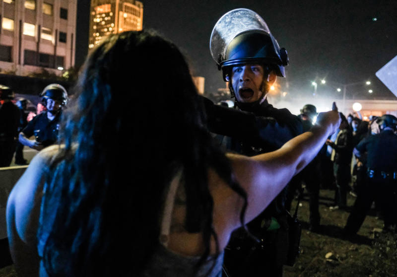A protester (foreground) confronts a police officer as demonstrators shut down the 101 Freeway in Los Angeles Wednesday night.