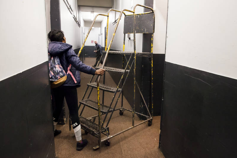 Brittany Jones pushes a set of portable stairs down the hallway of her storage unit.