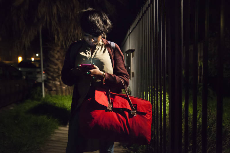 Brittany Jones checks her phone on her way to her grandmother's house in Richmond. Her bright red bag carries all off her clothes she'll need for the weekend before she goes back to her storage unit for more.