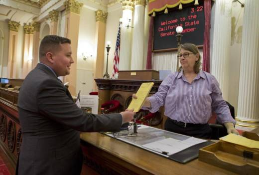 In the state Senate, Bernadette McNulty greets bill-bearing aides and assigns bill numbers.
