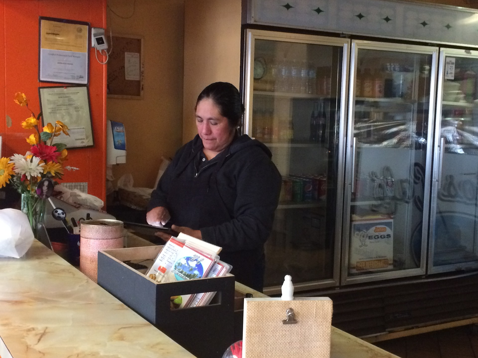 Edith Gallegos works the register at Hornitos Cafe, blocks away from the Ghost Ship warehouse fire. Gallegos said her clientele plummeted during recovery efforts at the fire site, which closed nearby streets.