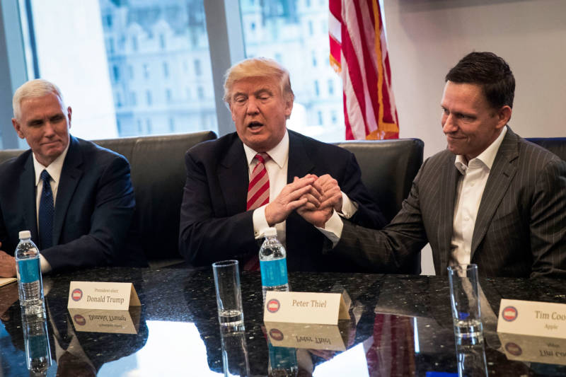 Mike Pence looks on as Donald Trump shakes the hand of Peter Thiel during a meeting with technology executives.