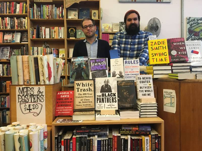 Store manager Ryan Smith (left) and Dan Weiss (right) in front of the book section Weiss created in response to Donald Trump's election.