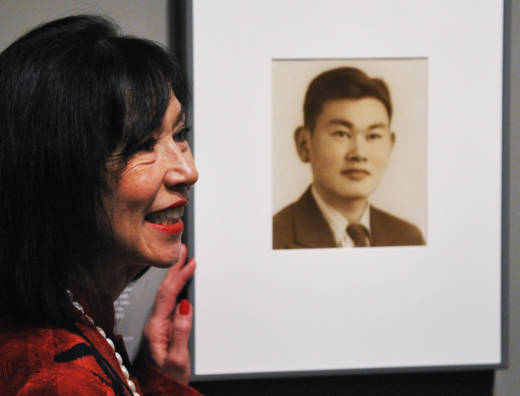 Karen Korematsu poses next to a photograph of her father Fred Korematsu during a presentation of his portrait to the National Portrait Gallery on February 2, 2012 in Washington, D.C.