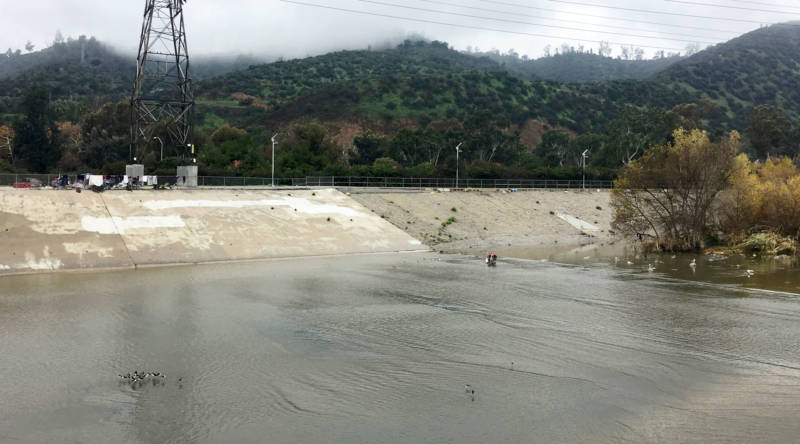 The L.A. River near Atwater Village is a flat, concrete flood control channel, designed to move water fast. Storm runoff can raise the river's level 10 feet and speed down the channel at 35 miles per hour. The islands where Wendy was living appear under the trees at right. Her present camp, at left, is approximately 50 feet higher up on the riverbank.