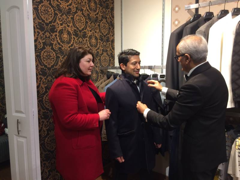 Juan Hernandez looks for a coat to wear to the presidential inauguration at Bossini USA in Santa Clara.