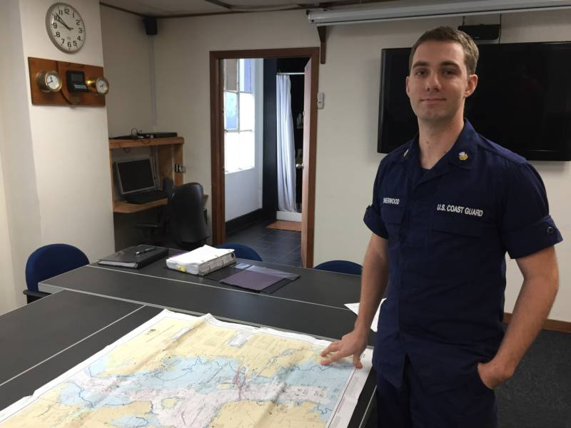 U.S. Coast Guard Petty Officer John Sherwood poses with a map of sound signals across the San Francisco Bay.