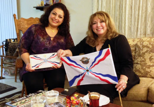 Mervat Shlemoun (L) and Carmen Morad hold up Assyrian flags.