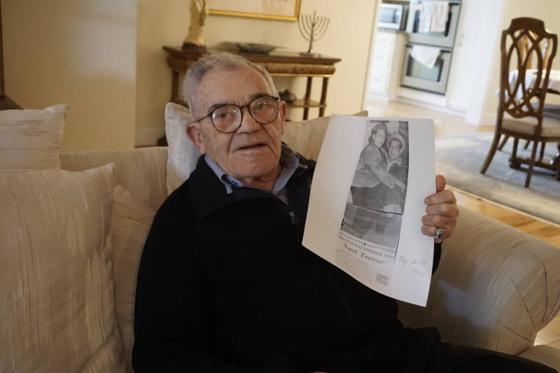 Ben Stern holds up a copy of a newspaper clipping show him and his wife after they came to the United States as Jewish refugees after World War II. Stern survived two ghettos, nine concentration camps and two death marches.