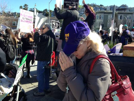 An unidentified anti-abortion activist prays at a demonstration outside the Planned Parenthood clinic in San Francisco.