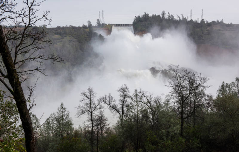 A huge spray cloud hangs over the Oroville Spillway as the California Department of Water Resources continues to release 100,000 cubic feet per second (cfs) from the damage spillway to decrease the lake level by 50 feet to handle the next round of storms expected this week. Photo taken February 13, 2017.