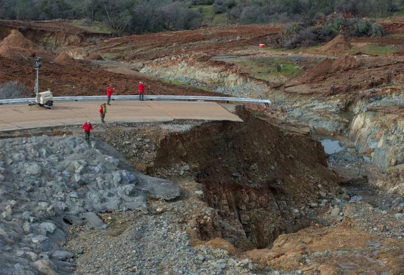 California Department of Water Resources crews inspect and evaluate the erosion just below the Lake Oroville Emergency Spillway site after lake levels receded on Monday morning. The outflow from the primary Oroville Spillway remains at 100,000 cubic feet per second (cfs) to decrease the lake level by 50 feet to handle the next round of storms this week. Photo taken February 13, 2017.