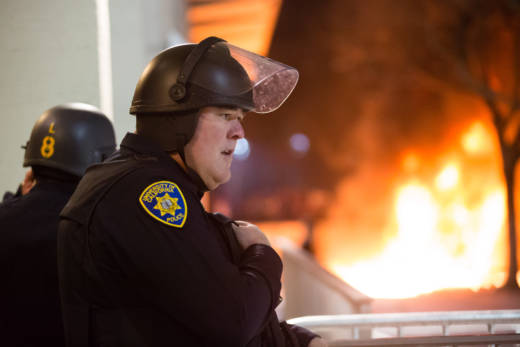 A campus police officer talks on his radio after protesters toppled a mobile light trailer and set it on fire during a demonstration against the scheduled appearance of Milo Yiannopoulos at UC Berkeley on February 1, 2017.