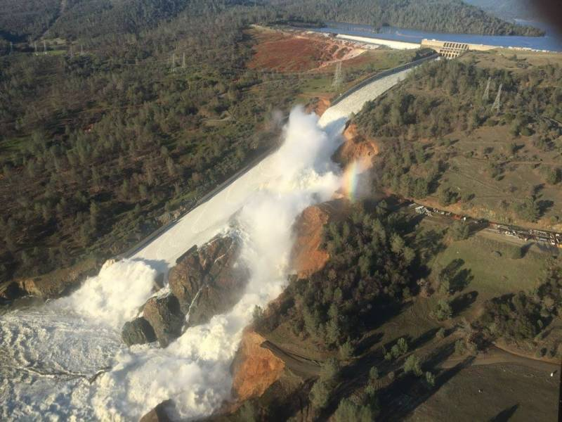 The damaged main Oroville Dam spillway next to the resultant severely eroded hillside.