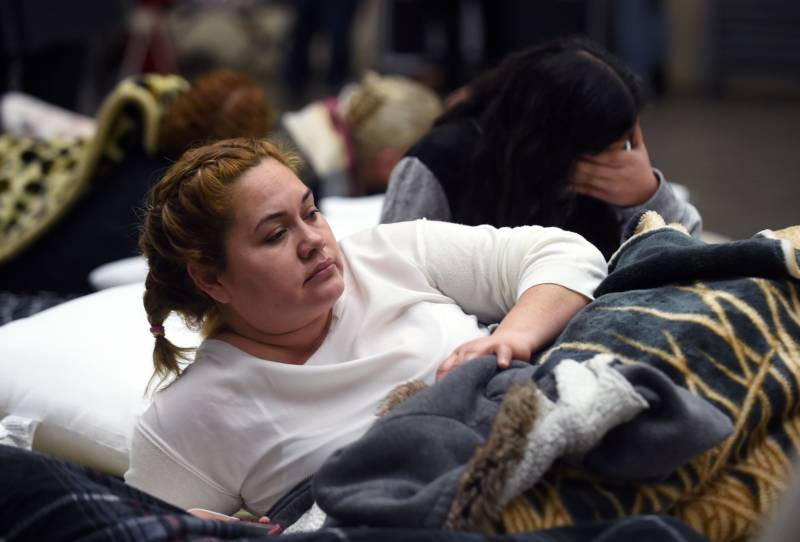 Evacuee Karina Garcia (L) looks on at the Placer County Fairgrounds evacuation center in Roseville, California on February 13, 2017. Almost 200,000 people were under evacuation orders in northern California Monday after a threat of catastrophic failure at the United States' tallest dam. Officials said the threat had subsided for the moment as water levels at the Oroville Dam, 75 miles (120 kilometers) north of Sacramento, have eased. But people were still being told to stay out of the area.