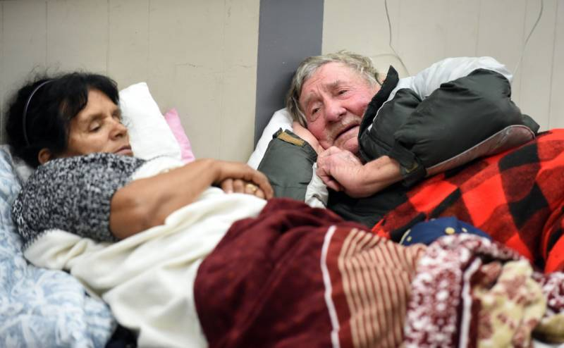 Evacuees Steve Allen (R) and Alicia Castro (L) lay on a cot at the Placer County Fairgrounds evacuation center in Roseville, California on February 13, 2017. Almost 200,000 people were under evacuation orders in northern California Monday after a threat of catastrophic failure at the United States' tallest dam. Officials said the threat had subsided for the moment as water levels at the Oroville Dam, 75 miles (120 kilometers) north of Sacramento, have eased. But people were still being told to stay out of the area.