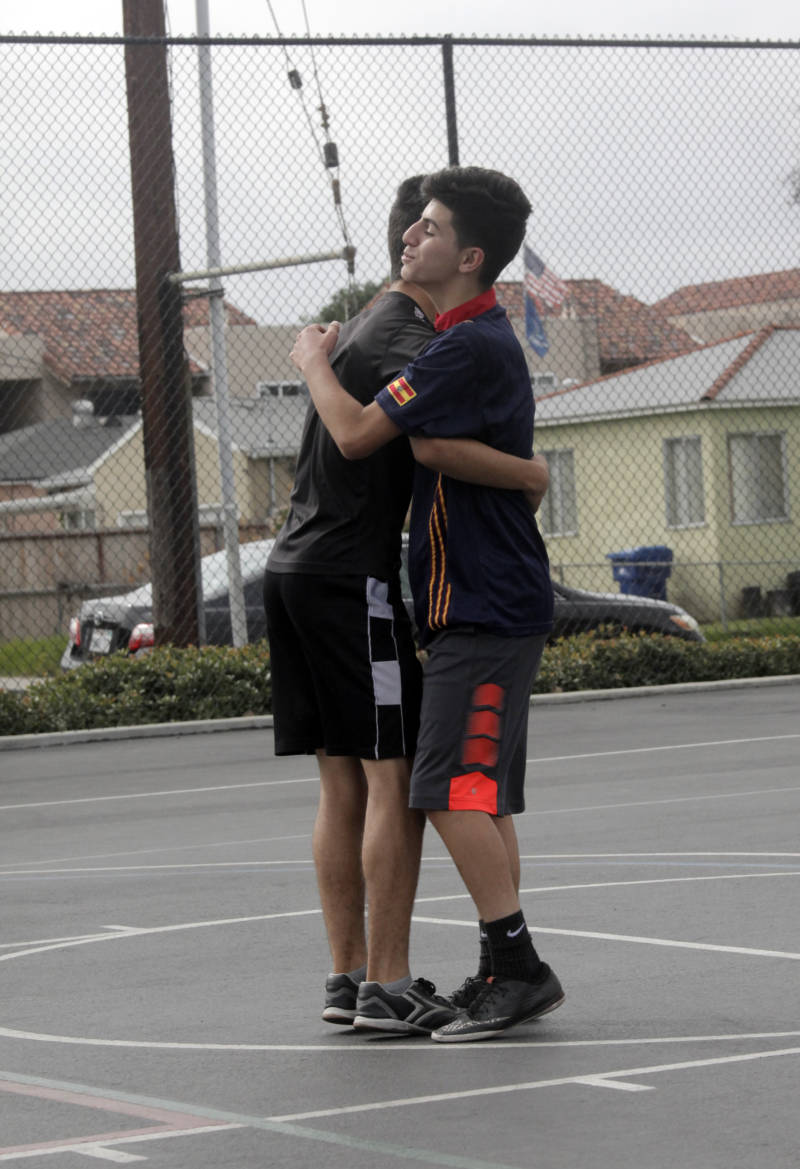 Osama Abdulazeez (right) hugs teammate Dani Matti during a pick-up soccer game.