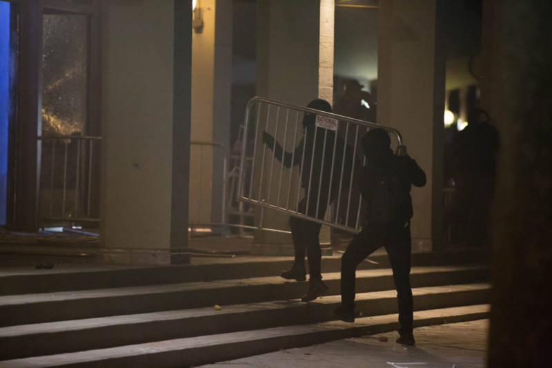 Militant protesters used police barricades to break windows on the Martin Luther King, Jr. Student Union building during a demonstration against the scheduled appearance of Milo Yiannopoulos at UC Berkeley on Feb. 1, 2017.