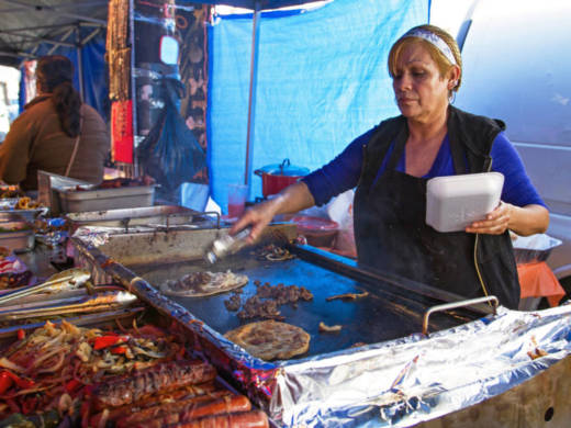 A street vendor makes huaraches and quesadillas on the sidewalk in Los Angeles. LA is the only major U.S. city where selling food on the sidewalk is illegal. President Trump's immigration policies have pushed the city council to change the law. But the devil is in the details.