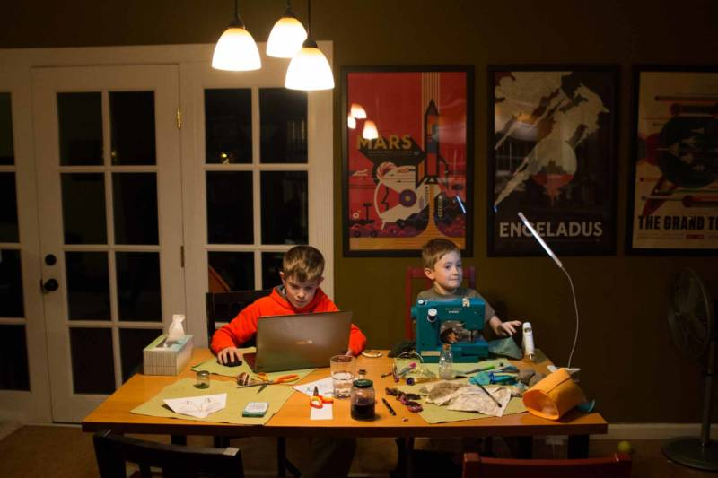 Ryan and Nicolas Halstead work on their homework after school in Napa, CA. Ryan is sewing, while his brother is learning to code.
