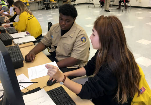 Floyd Maxey (L), a freshman at Alain Leroy Locke College Preparatory Academy, a charter high school in South L.A., goes over his grades with City Year corps member Eleanor Kim.