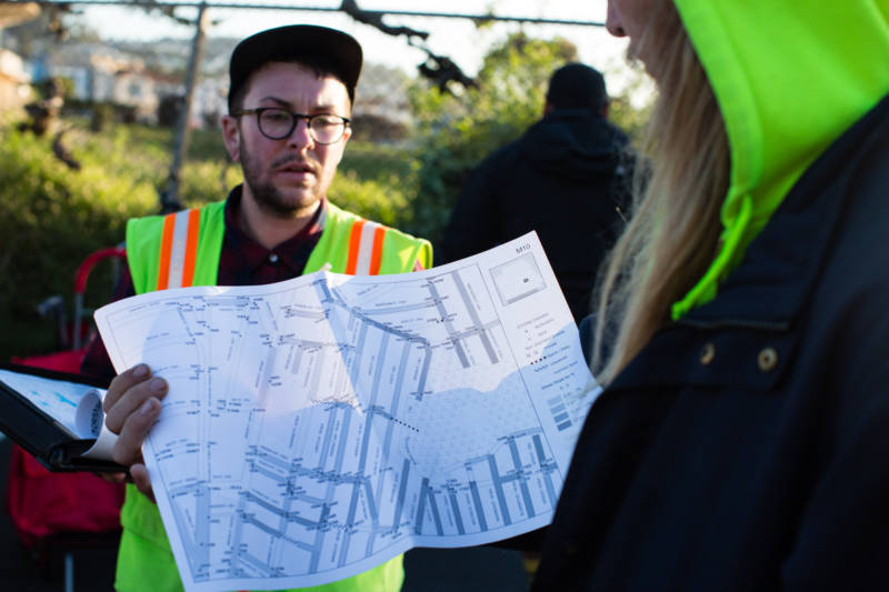 Lorae Fernandis (left) briefs Kevin Lash (right) on his route for mosquito abatement in San Francisco on the morning of March 23, 2017. They and other members of the Mosquito Abatement Courier (MAC) crew distribute larvicide tablets throughout the city's storm drains by bicycle.