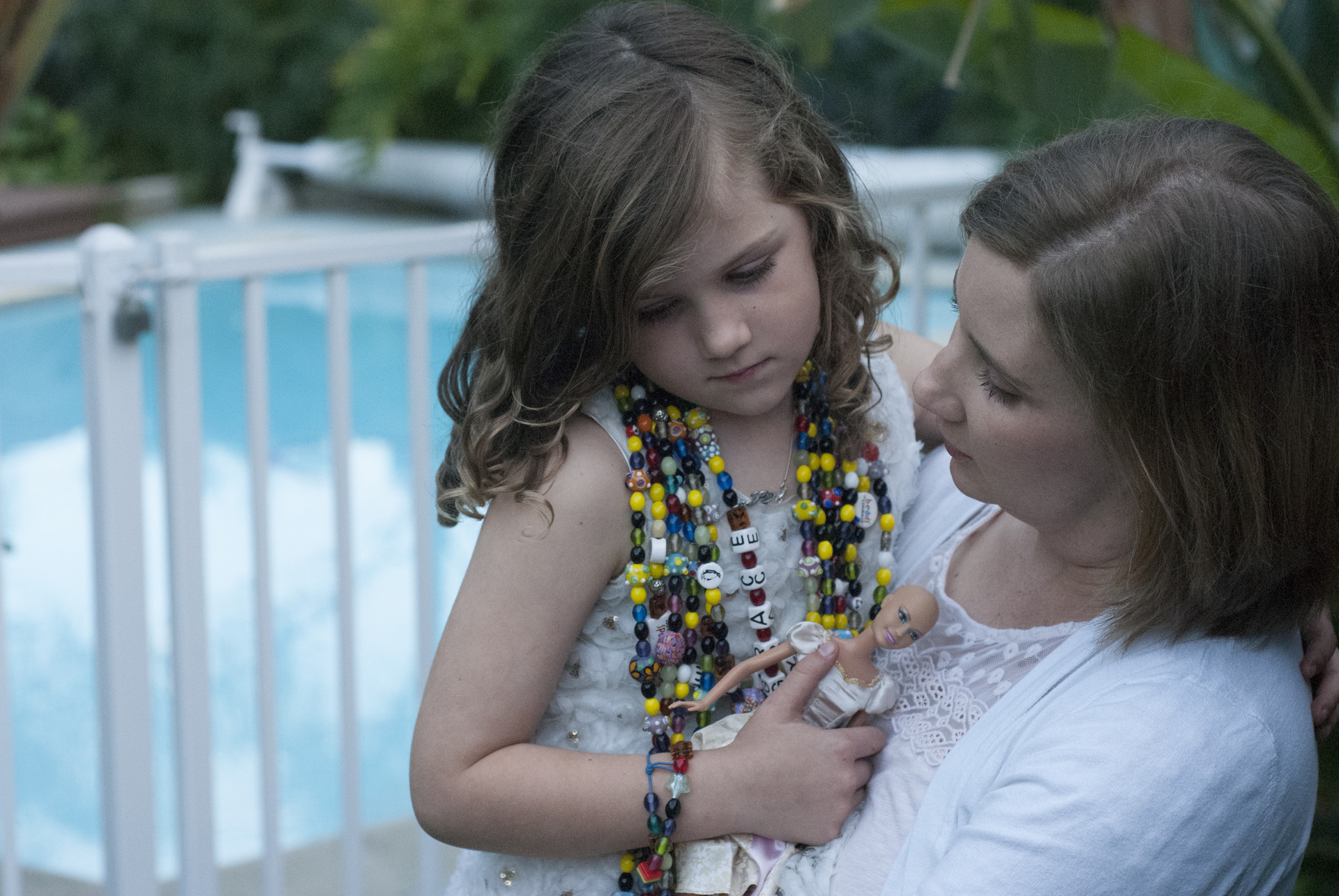 "Gracie Bumstead, 7, was diagnosed at age 4 with a rare form of leukemia. The necklace she wears is made of ""courage beads"" she received each time she completed a chemotherapy treatment. She's been cancer-free since January 2016. Gracie's mother Melissa, right, says neighborhood children have an unusually high cancer rate."