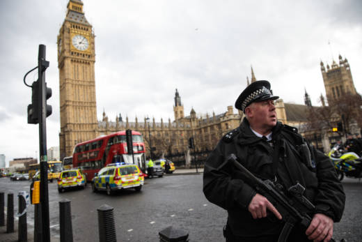 An armed police officer stands guard near Westminster Bridge and the Houses of Parliament on Wednesdayin London, England.