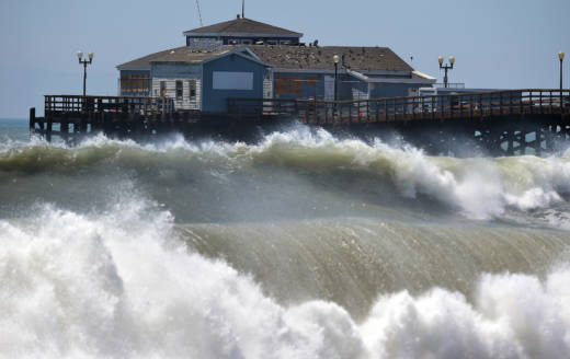 Large waves crash ashore and into the pier at Seal Beach in 2014.