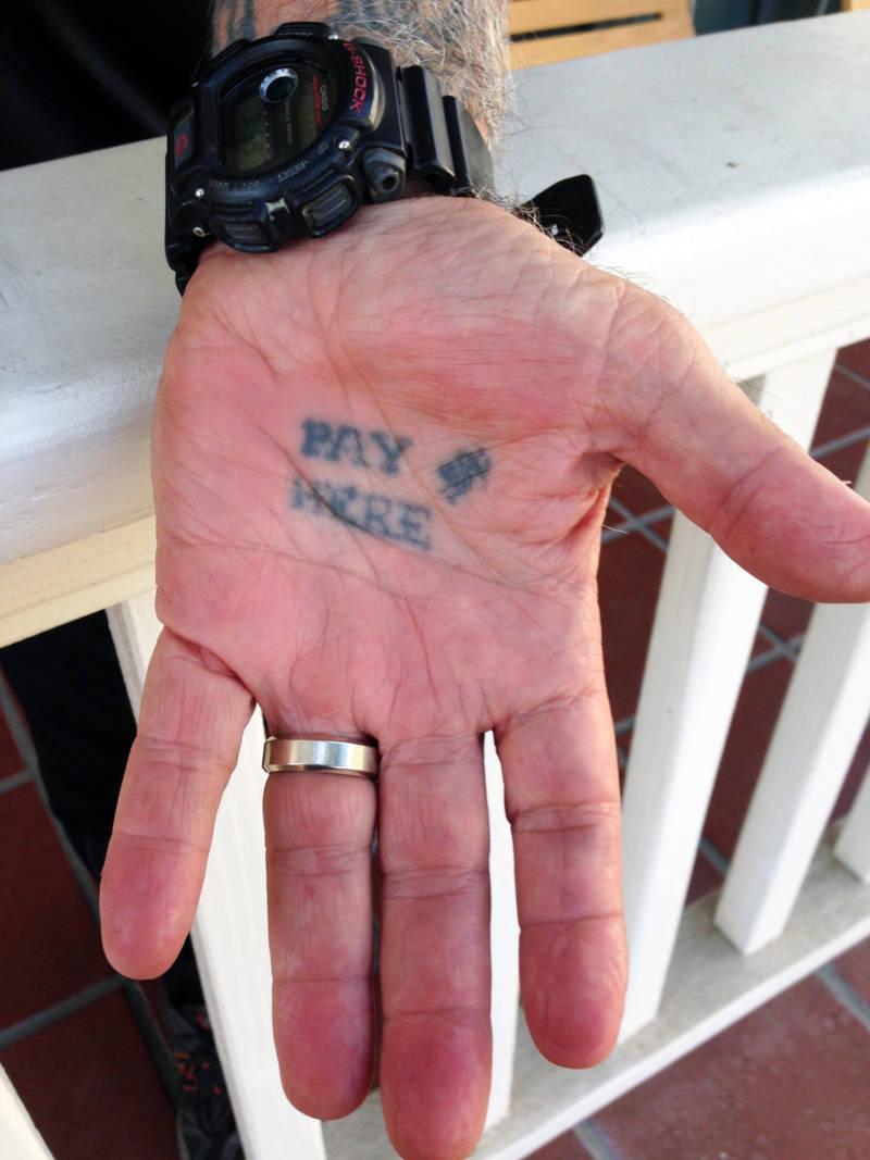 George Christie's palm bears a distinctive tattooed directive.