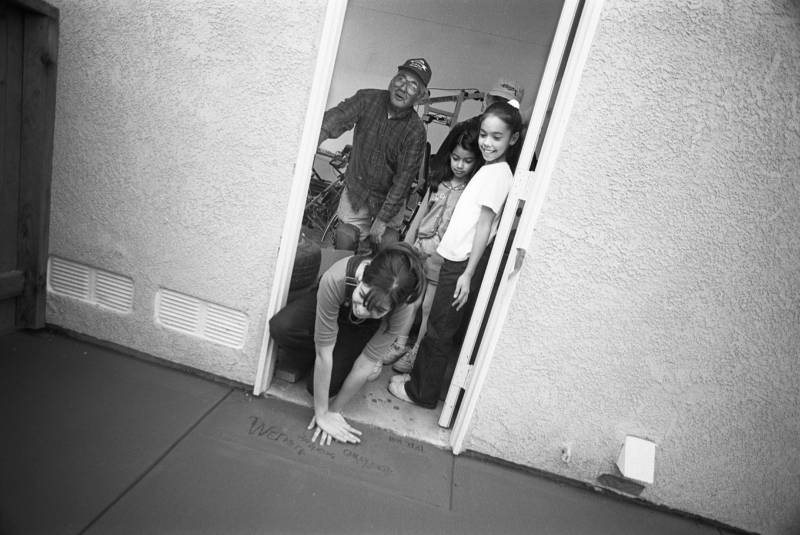 Augie Cortez' daughters press their hands into the wet cement of their new Dream Street home while his father looks on.