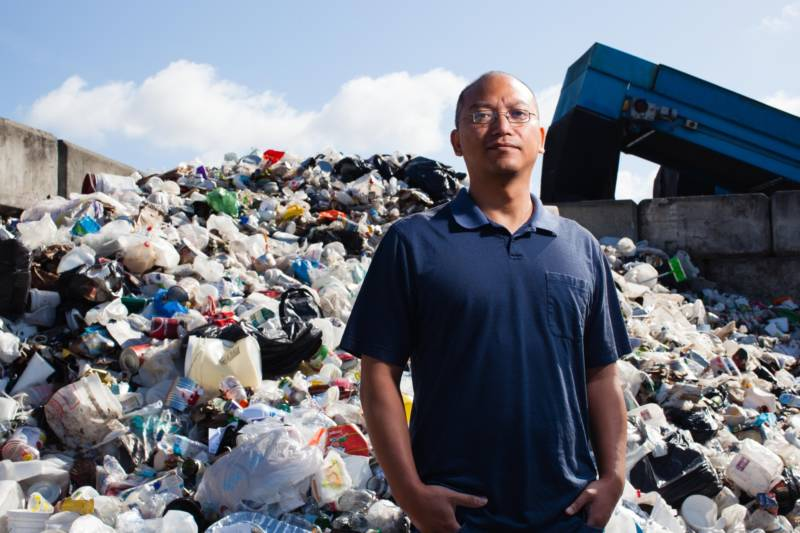 Daniel Maher stands in front of a pile of recycling at the Berkeley Ecology Center.