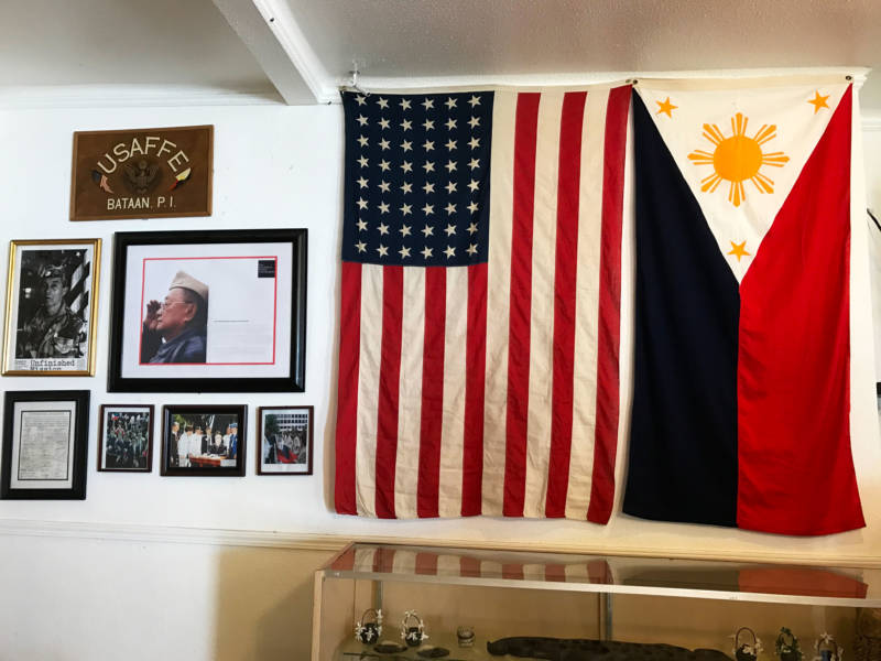 Tess and Marco visit a community center where the flags of the United States and the Philippines are displayed next to images of Filipino veterans of the United States Army Forces in the Far East (USAFFE).