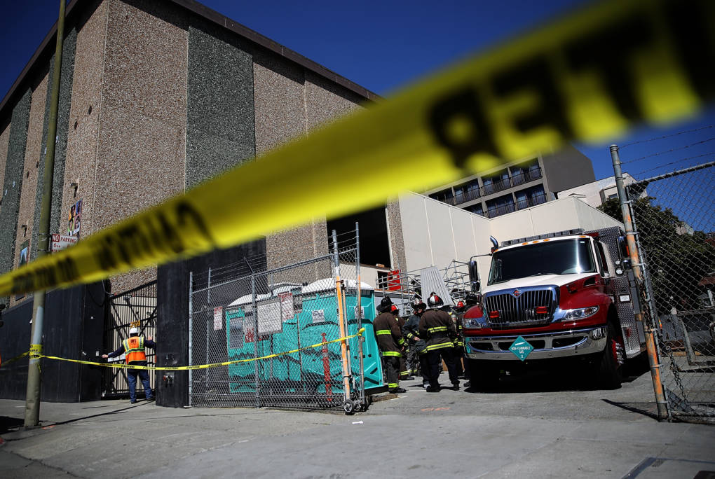 San Francisco fire department crews stand outside of an electric substation where a fire occurred and might have caused the outage.
