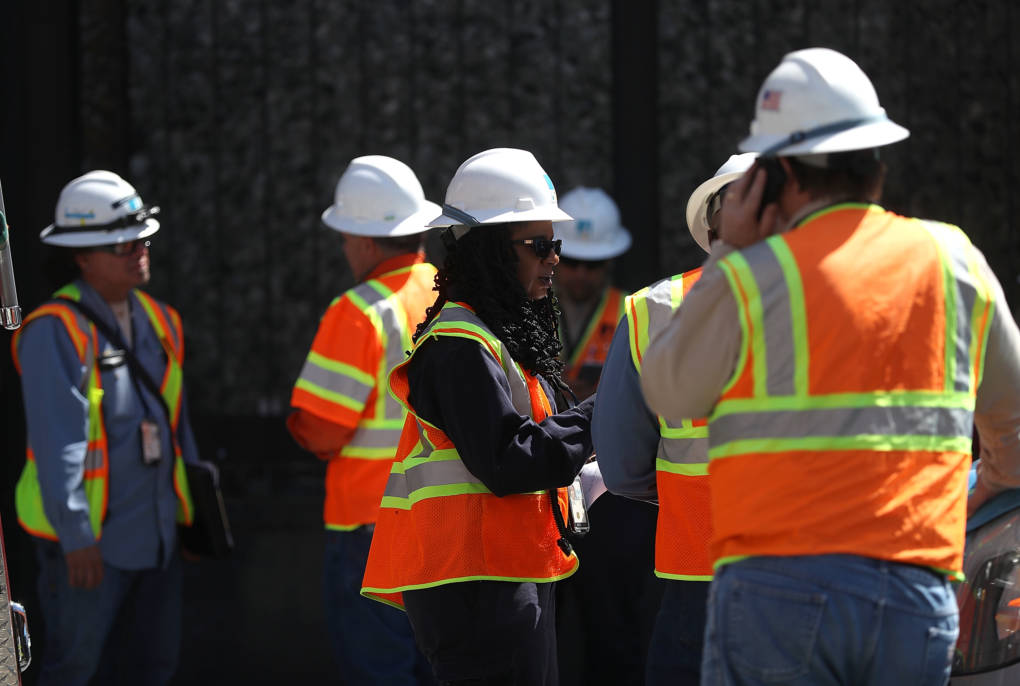 PG&E workers stand outside of an electric substation where a fire occurred and might have caused the outage.