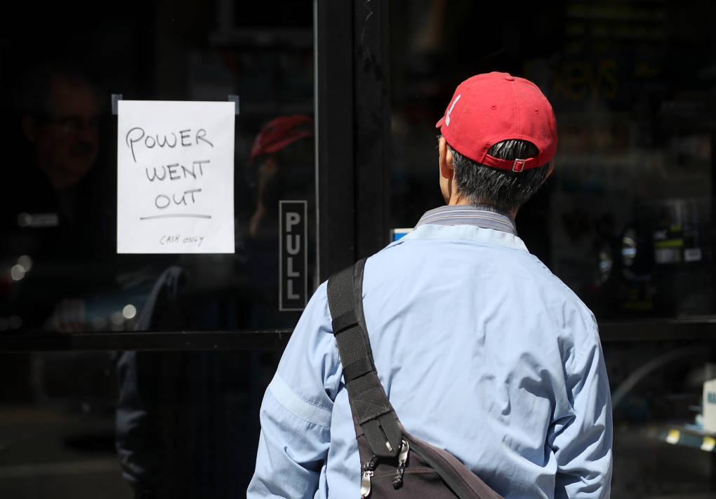 A pedestrian looks at a sign posted on the door of a hardware store.