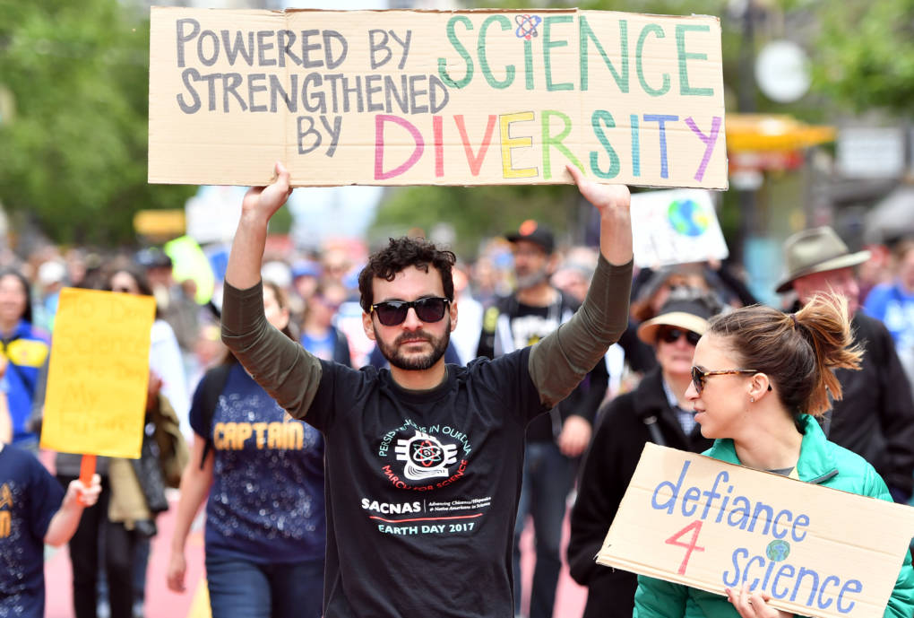 Raul Tores (C) holds up a sign during the March for Science in San Francisco,