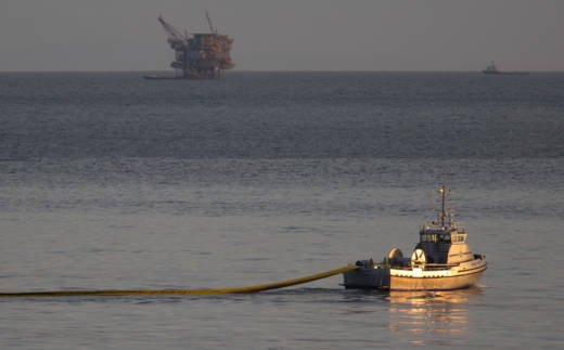 A boat deploys a boom, with an oil platform seen in the distance, to try to contain an oil spill on May 19, 2015 north of Goleta.