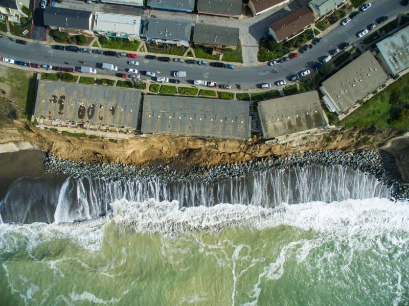 Apartment buildings hang perilously over an increasingly eroded bluff in Pacifica.