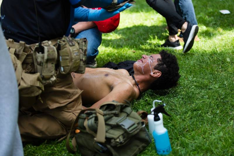 A volunteer medic washes a protester's face with milk after he was exposed to pepper spray on April 15, 2017. Berkeley police arrested at least 21 people during a pro-Trump rally that became violent after counter-protesters clashed with demonstrators.