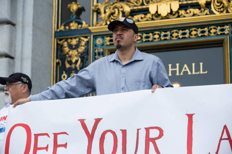Sergio Estrella, a member of SEIU Local 87, held a banner during a press conference in front of San Francisco City Hall on April 24, 2017. He appeared with members of the May 1st Coalition, who were announcing their participation in the upcoming May Day protest.