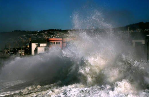 A large wave crashes against a seawall near Pacifica.