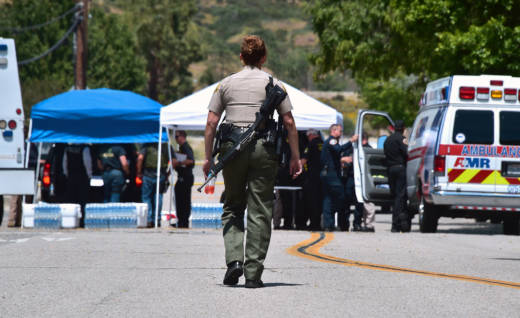 An armed law enforcement officer walks outside the closed-off North Park School in San Bernardino on April 10, 2017, following a shooting at the elementary school.