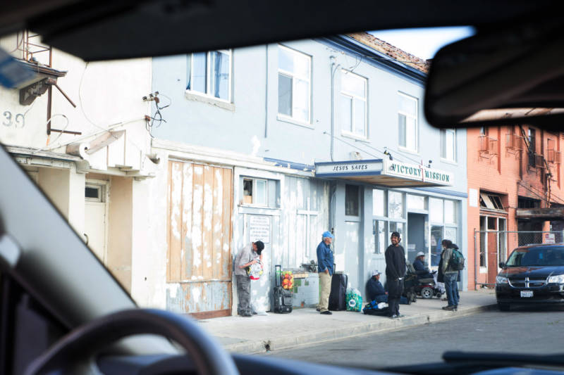 The view out of Commander Crabill's police vehicle shows homeless residents standing outside Victory Mission, a homeless services center in Salinas' Chinatown.