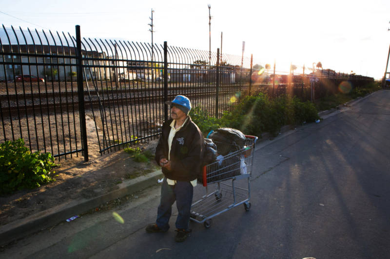 A man rests from pushing his cart as the sun sets behind the railroad tracks in Salinas' Chinatown.